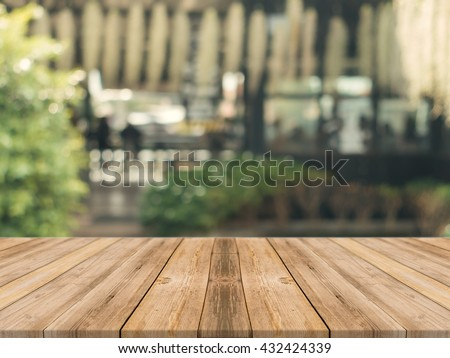 Wooden board empty table in front of blurred background. Perspective brown wood over blur in coffee shop - can be used for display or montage your products.Mock up for display of product.