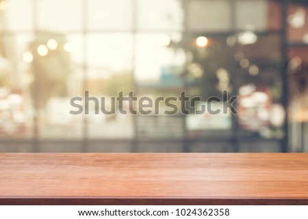 Wooden board empty table top on of blurred background. Perspective brown wood table over blur in coffee shop background -