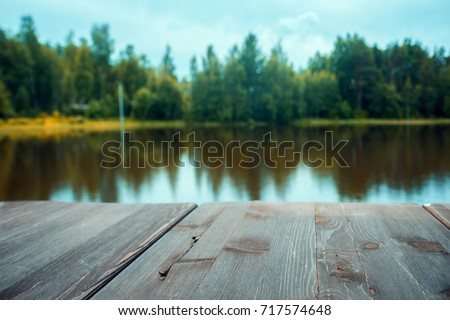 Wooden board lake with autumn  forest and lake at the background with wooden floor. can be used for display or montage your products.Mock up for display of product.
