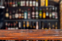 Wooden board on a background of bottles with alcohol. Old bar counter as layout for design. Workpiece for design. Empty place to advertise products. Blurred interior of the bar in the background.