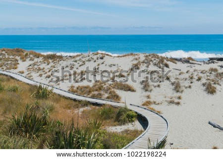 Wooden board walk over sand beach with ocean skyline, natural landscape background