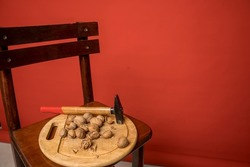 Wooden board with a hammer and plenty of walnuts on a kitchen chair