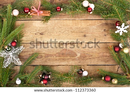wooden board with Christmas motifs,  green fir branches with red and white christmas balls