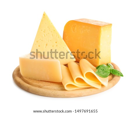 Wooden board with different kinds of cheese and basil on white background