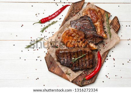 Wooden board with different tasty cooked meat and spices on white table #1316272334