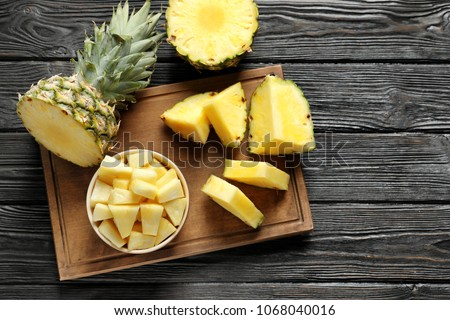 Wooden board with fresh sliced pineapple on table, top view ストックフォト ©