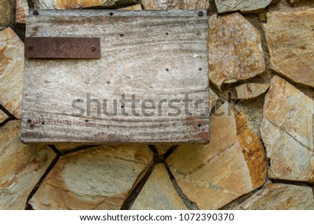 Wooden Board With Iron Plate Sticked On Rock Wall 1072390370