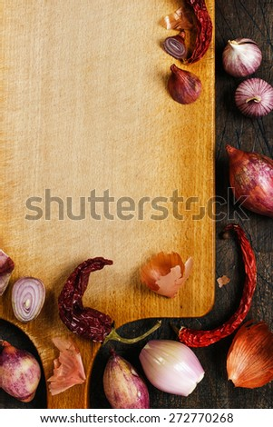 Wooden board with onions, garlic and pepper background vertical