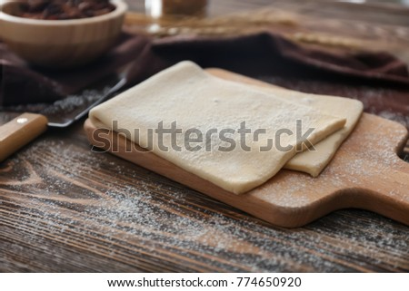 Wooden board with raw flaky dough on table ストックフォト ©
