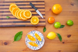 Wooden board with sliced orange and knife. Three orange pieces laying on ceramic plate with floral pattern. Limes and lemon on table. Top view. Studio shot. Nutrition and vegetarian concept