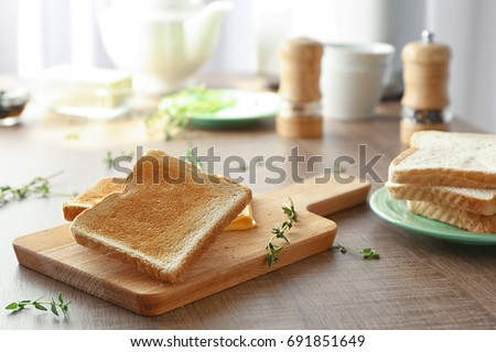 Wooden board with tasty breakfast toasts on table
