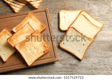 Wooden board with tasty toasted bread on table ストックフォト ©