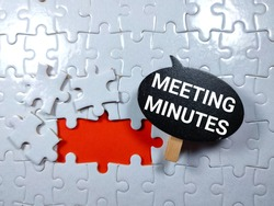 Wooden board with text MEETING MINUTES on puzzle background.Business concept.