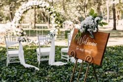 Wooden board with Welcome to our event text at a wedding on aisle background.