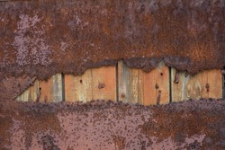 Wooden boards covered with metal with a hole inside. Old destroyed door close-up