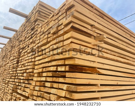 Wooden boards, lumber, industrial wood, timber. Pine wood timber stack of natural rough wooden boards on building site. Industrial timber building materials.