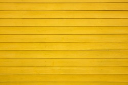 Wooden boards painted with yellow paint. Background Texture