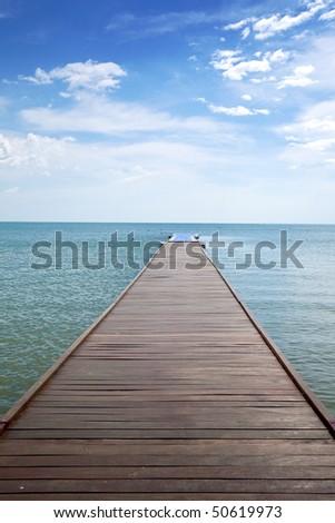 Wooden boardwalk above water out towards open ocean