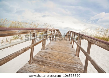 Wooden boardwalk at the beach leading to the surf and ocean through the dunes.