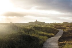 Wooden boardwalk leading in grassy seaside landscape to lighthouse. View against sunshine. Cloudy sky. Summer vacation concept.