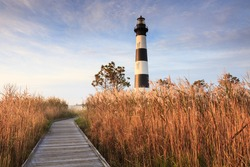 Wooden boardwalk leading through the marsh to the Bodie Island Lighthouse on the Cape Hatteras National Seashore on the Outer Banks in North Carolina.
