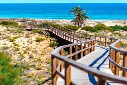 Wooden boardwalk on the Los Arenales del Sol beach. Alicante province, Costa Blanca. Spain