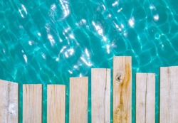 Wooden boardwalk on the seawater background. The sea is bright blue on a nice day. The beauty of nature in the summer. Gives a feeling of calmness, coolness, and comfort.