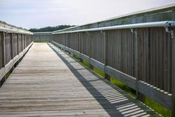 Wooden boardwalk with metal railings over coastal marsh