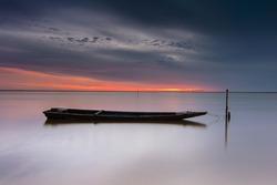 wooden boat bound at wooden pole at Jubakar Pantai, Tumpat, Kelantan East coast of Malaysia.