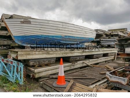 Wooden boat on stacks of old mooring pontoons. Scrap wood piles in small boatyard