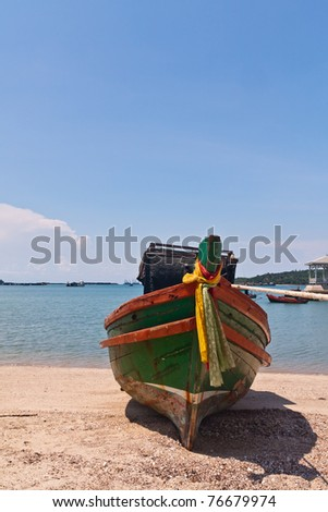 Wooden boat on the beach with beautiful blue sky in background in Thailand from front vertical
