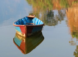 wooden boat on the lake, reflection of the bat in the lake,fishing boat in a calm lake water.