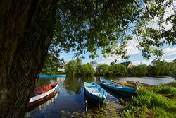 Wooden boat on the river bank with brown water against the blue sky. Summer landscape in the village