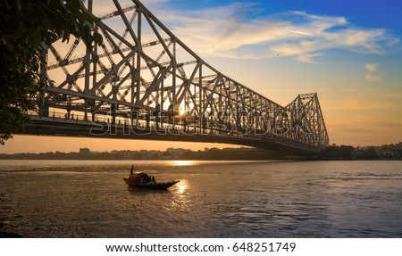 Wooden boat passing the historic Howrah bridge in silhouette at sunrise. Howrah bridge is a cantilever bridge on the river Hooghly and one of the busiest bridge in the world. #648251749