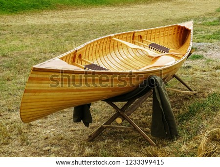 Wooden boat placed on a wooden stand in the meadow.After the boat and over the stand there is a blanket.In the boat there are two rowing boats and two knit benches.The boat is new.     #1233399415