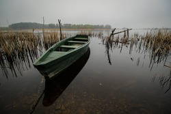 Wooden boat reflected in lake on a foggy day.