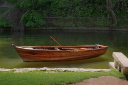 Wooden boat standing near river bank in park, solitude and calmness, relaxation