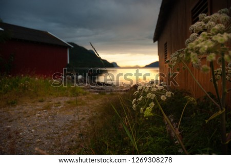 Wooden Boathouses at Sunset with an Overcast Sky #1269308278