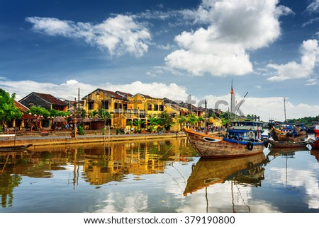 Wooden boats on the Thu Bon River in Hoi An Ancient Town (Hoian), Vietnam. Yellow old houses on waterfront reflected in river. Hoi An is a popular tourist destination of Asia. Stockfoto ©