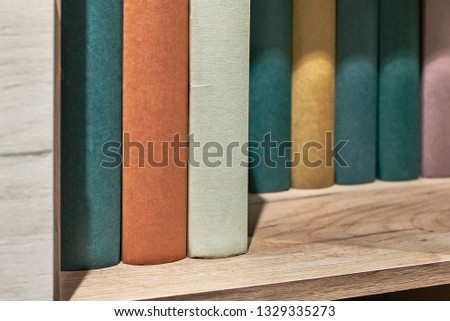 Wooden book shelf with series of books, no titles shown, blank sides #1329335273