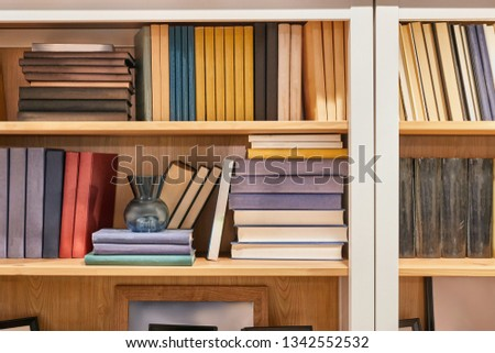Wooden book shelf with series of books, no titles shown, blank sides #1342552532