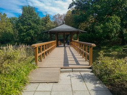 Wooden bower with wooden bridge in japanese garden