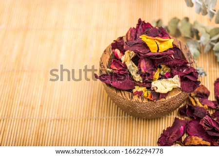 Wooden bowl and colored petals, decorated with branches on wooden background. Foto stock ©