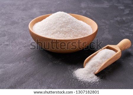Wooden bowl and scoop with powdered white sugar  on on a black background