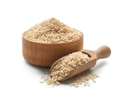 Wooden bowl and scoop with sesame seeds on white background