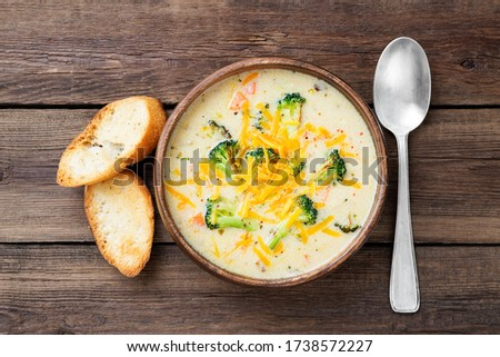 Wooden bowl of creamy broccoli cheddar cheese soup with toasted bread top view
