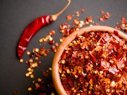 Wooden bowl of crushed red pepper, Cayenne pepper, dried chilli on a motley background. It is a popular spicy condiment for Mexican dishes. Top view.