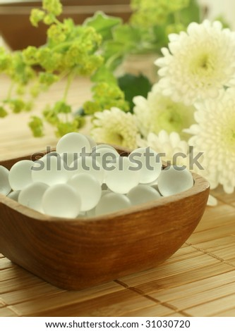 Wooden bowl of decorative balls and flowers