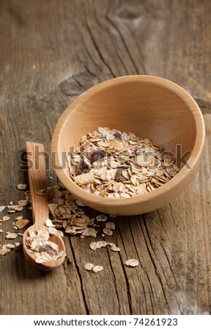 Wooden bowl of dry muesli and wooden spoon on old wooden desk