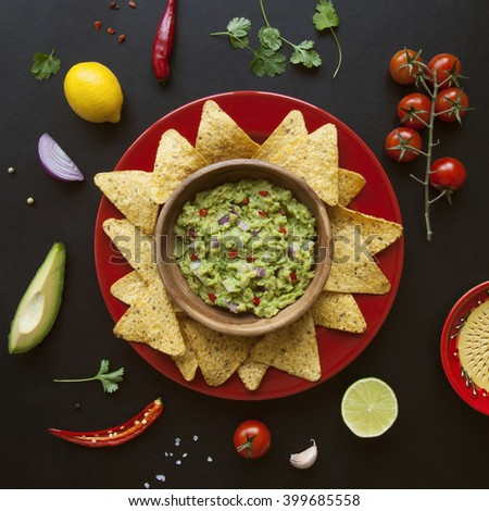 wooden bowl of fresh homemade guacamole, its ingredients and nachos chips on black background from above #399685558